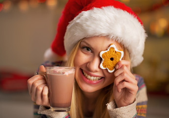 Portrait of happy girl in santa hat with christmas cookie