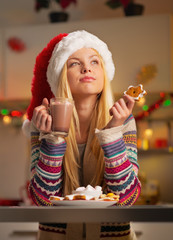 Thoughtful teenager girl in santa hat with christmas cookie
