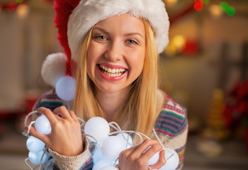 Portrait of happy teenager girl in santa hat holding garland