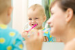 mother and kid look at mirror during teeth brushing - 74434918