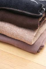 pila di maglioni di  lana su tavolo di legno