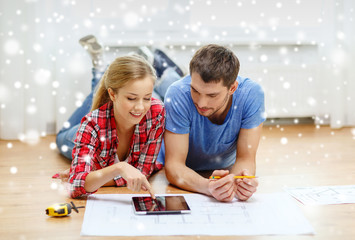smiling couple with tablet pc at home