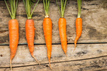 Fresh ripe carrots lying on wooden background.
