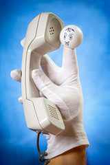 Finger puppet holding wired phone handset over blue background