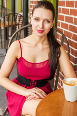 Beautiful young Latvian woman at cafe with latte on table