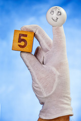 Number five on wooden cube hold by finger puppet