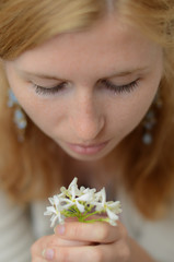 Red-haired girl with freckles looking at white flowers