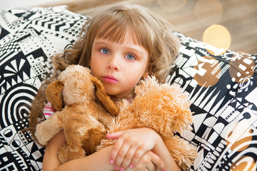 Little girl holding a soft toys at home.