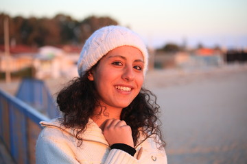 Smiling young sicilian girl near the beach at sunset