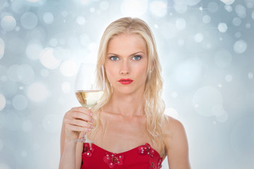 nordic girl holding a glass of wine on a silver gleaming backgro