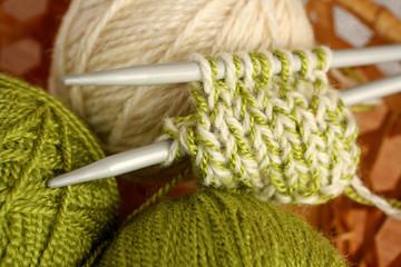 Knitting needles, skeins of wool in a wicker basket