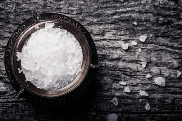 sea salt in an old utensils on wooden table