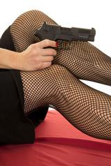 woman legs in black fishnets hold pistol point