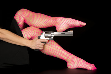 woman legs in pink fishnet hold gun