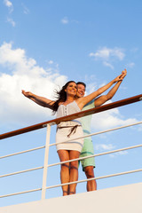 young couple with arms outstretched on cruise ship