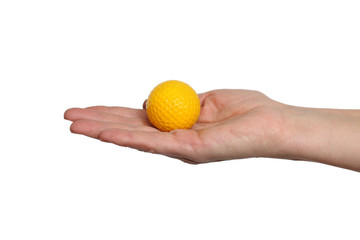 Yellow golf ball in hand isolated on white background