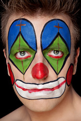 Young man in clown makeup in the studio on a black background