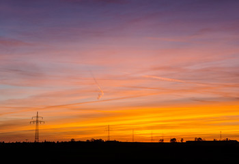 power line silhouettes in front of a colorful sunset sky