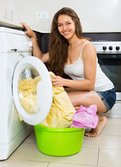 Nice young woman washing clothes in washer