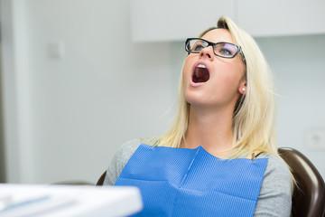 Junge Dame / Patientin mit Mund auf wartend in Zahnarztstuhl
