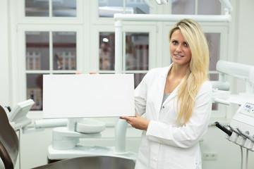 Junge Frau / Zahnarzt Helferin hält weißes Schild vor Behandlung