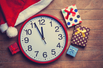 Clock and christmas hat with gifts on wooden table.