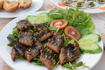 Close up of fried eel with vegetables and greens