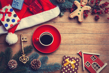 Cup of coffee with pine branch and christmas gifts on wooden bac