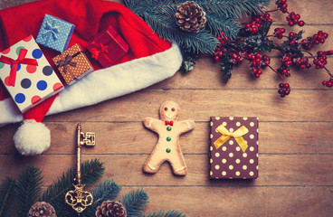 Gingerbread man and gift on wooden table.