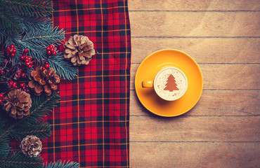 Cappuccino and  pine branch with tartan on wooden table.