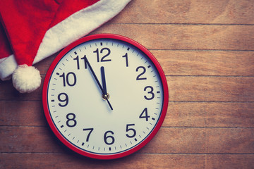 Clock and christmas hat on wooden table.
