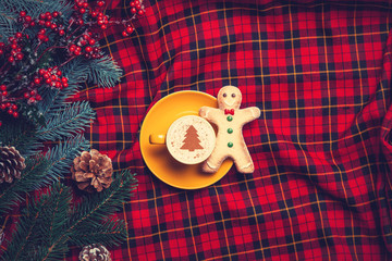 Cappuccino with gingerbread man and pine branch on tartan backgr