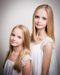 Two Beautiful Blond Teenage Girls Dressed in White.