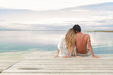 Fototapety man and woman couple sitting on a Jetty under a blue cloudy sky