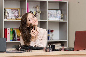 Girl in the office with brushes for make-up