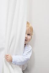 baby peeking behind curtain