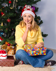 Young woman holding gift and sits near Christmas tree