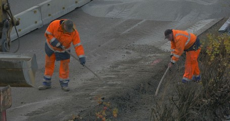 Two construction workers shoveling gravel on highway