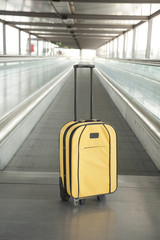 yellow suitcase at walkway