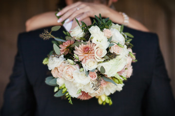 Bride with a bouquet in the hands of the hugging groom