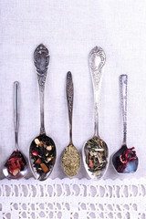 Tea in metal spoons on lace fabric background