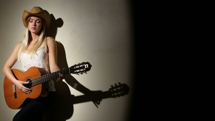 Cute girl plays on the acoustic guitar with bright emotions -