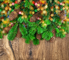 christmas tree branches with cones and colorful lights