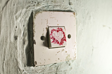 Old light switch with red paint heart on old cracked green wall