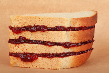 Tasty sandwich with jam, on brown background