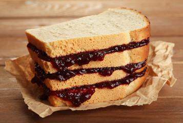 Tasty sandwich with jam on wooden table