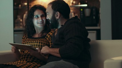 Couple using tablet on sofa at night in room