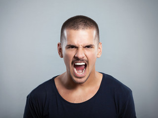 Portrait of a furious young man shouting. Studio shot.