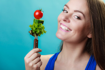 woman holding fork with vegetables