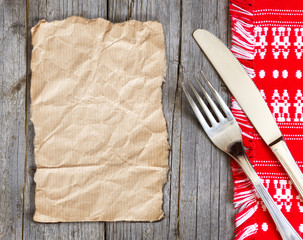 Paper, fork and knife on kitchen towel